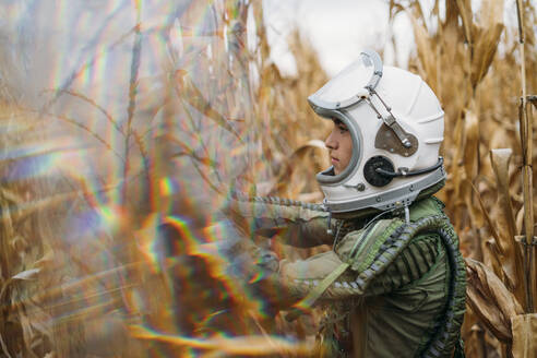 Young spaceman standing in wilted corn field - JCMF00450