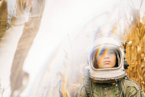 Young spaceman standing in wilted corn field - JCMF00453