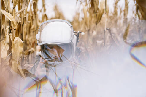 Young spaceman standing in wilted corn field - JCMF00456