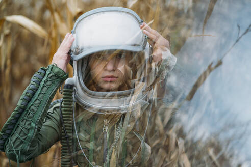 Young spaceman standing in wilted corn field - JCMF00459