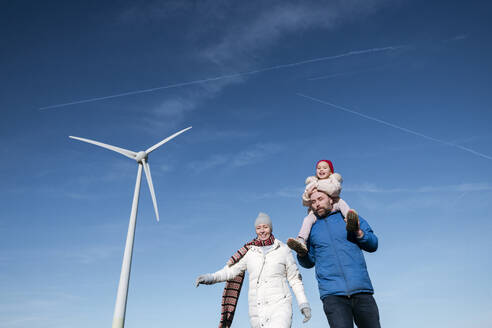 Parents with little daughter against with wind wheel in the background - VYF00070