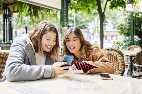 Two happy young women with smartphone at an outdoor cafe - DGOF00556