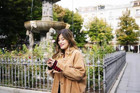 Smiling young woman using smartphone in the city - DGOF00562
