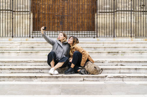 Two happy young women sitting on stairs in the city taking a selfie - DGOF00571
