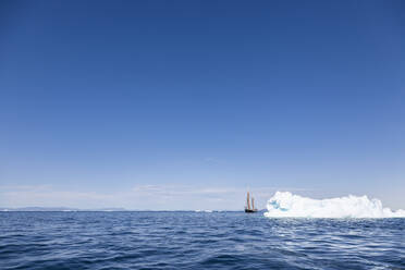 Ship sailing behind iceberg on sunny blue Atlantic Ocean Greenland - HOXF05791