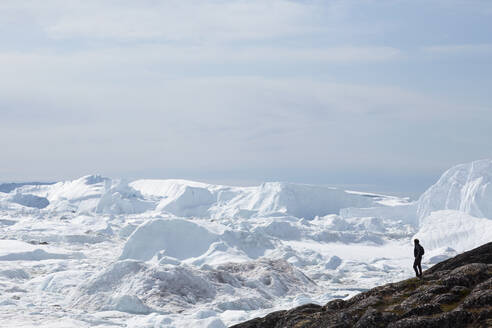 Man standing on cliff overlooking glacial ice melt Greenland - HOXF06130