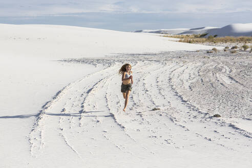 A teenage girl running in the sand, - MINF14299