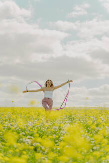 Happy young woman moving with colourful ribbons in a flower meadow in spring - ERRF02878