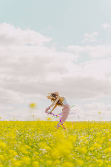 Happy young woman moving with colourful ribbons in a flower meadow in spring - ERRF02881