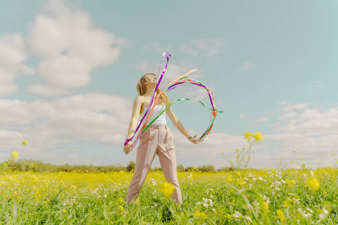 Happy young woman moving with colourful ribbons in a flower meadow in spring - ERRF02887
