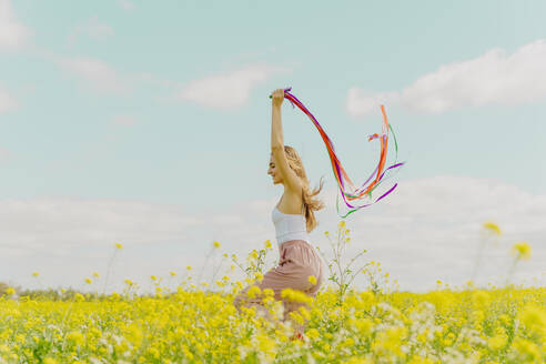 Happy young woman moving with colourful ribbons in a flower meadow in spring - ERRF02902