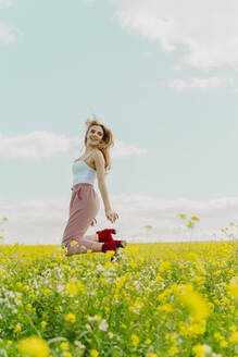 Happy young woman jumping in a flower meadow in spring - ERRF02911