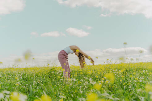 Young woman bending over in a flower meadow in spring - ERRF02920