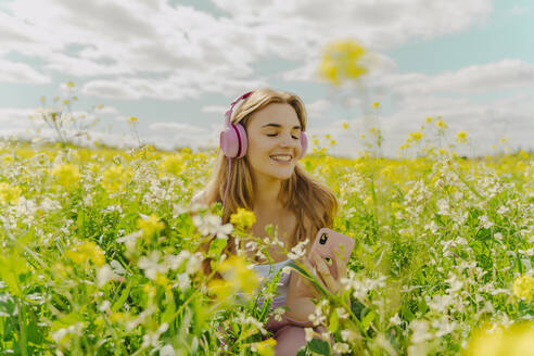 Happy young woman with headphones and smartphone in a flower meadow in spring - ERRF02929