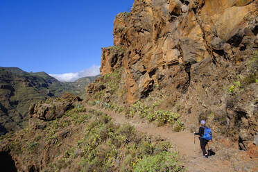 Spain, Province of Santa Cruz de Tenerife, San Sebastian de La Gomera, Rear view of senior backpacker hiking at Alto de Tacalcuse - SIEF09670