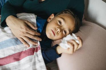 Portrait of sick little boy lying in bed - JRFF04241