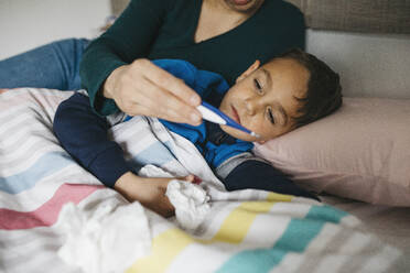Sick boy with tissue in his hand lying in bed looking together with his mother at digital thermometer - JRFF04244