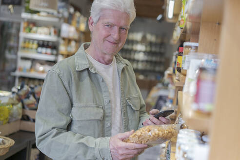 Portrait of senior man buying groceries in a small food store - AFVF05847
