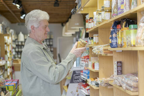 Senior man buying groceries in a small food store - AFVF05850