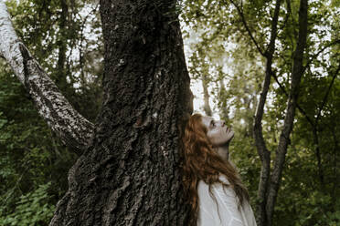 Young redhaired woman hugging tree trunk in forest - AFVF05928
