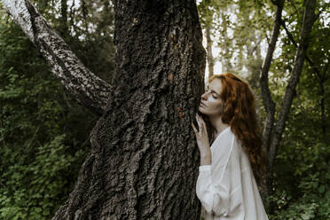 Young redhaired woman hugging tree trunk in the forest - AFVF05931