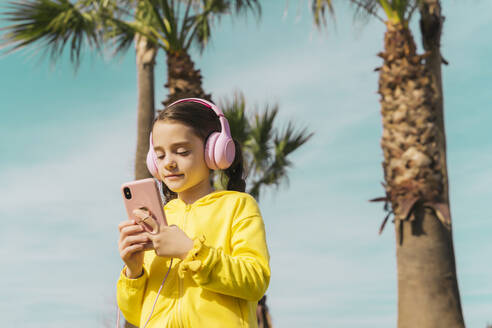 Portrait of little girl wearing yellow  jacket listening music with headphones looking at smartphone - ERRF02942