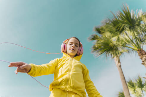 Portrait of little girl wearing yellow hooded jacket listening music with headphones - ERRF02948