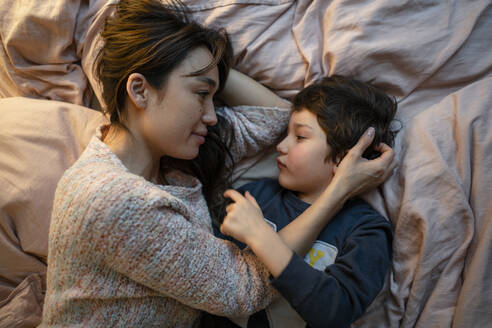 Mother and little son relaxing together on bed - KNSF07963