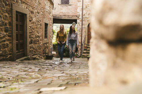 Two young women exploring picturesque old town, Greve in Chianti, Tuscany, Italy - JPIF00570