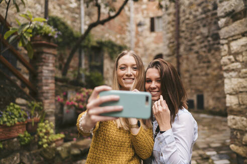 Two young women taking a selfie in picturesque old town, Greve in Chianti, Tuscany, Italy - JPIF00573