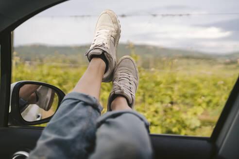 Woman's feet leaning out of car window - JPIF00579