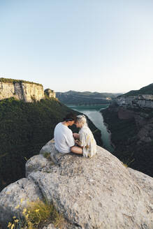Young couple in love sitting on viewpoint, Sau Reservoir, Catalonia, Spain - AMAF00011