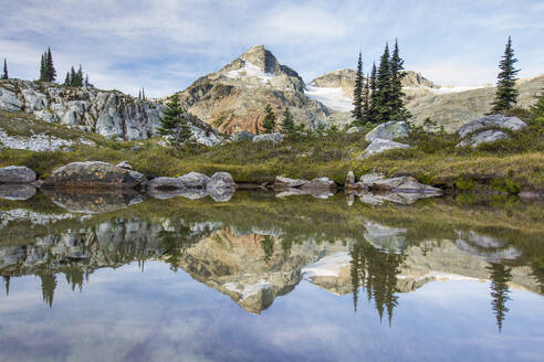 Alpine meadow and mountains reflecting in lake. - CAVF77937