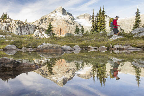 Side view and reflection of backpacker hiking beside alpine lake. - CAVF77940