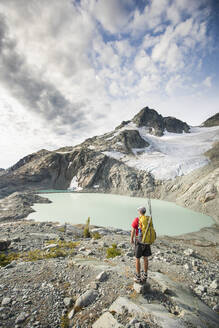 Backpacker stops to look at view of mountains glacier and lake. - CAVF77952