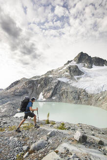 Backpacker hiking with view of lake and mountains - CAVF77955