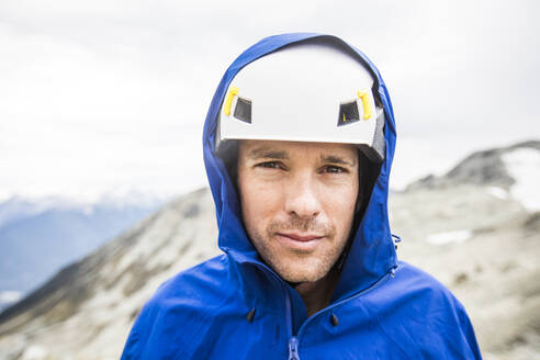 Portrait of mountain climber wearing helmet and rain jacket. - CAVF77973