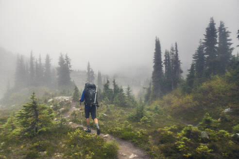 Rear view of backpacker hiking in the rain. - CAVF77985