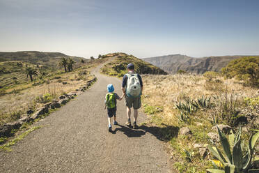 Back view of father and little son with backpacks walking hand in hand on country road, La Gomera, Canary Islands, Spain - IHF00292