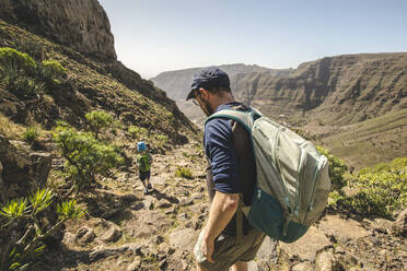 Father and little son with backpacks walking on a hiking trail in the mountains, La Gomera, Canary Islands, Spain - IHF00295