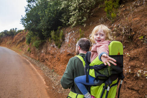 Father carrying his little daughter in a child carrier, La Palma, Canary Islands, Spain - IHF00298