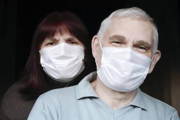 Portrait of senior couple wearing masks at home - EYAF00992