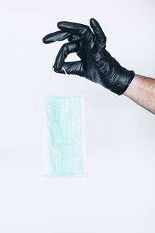 Hand in protective glove holding mask - JCMF00503