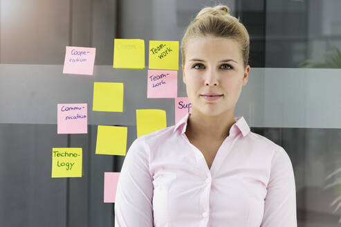 Young businesswoman, standing in front of adhesive notes - BMOF00340