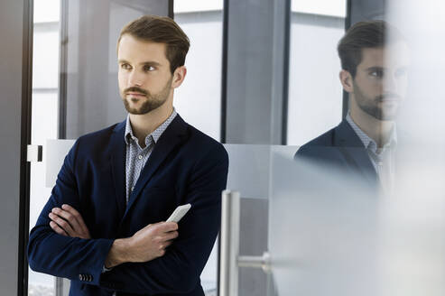 Portrait of young businessman with smartphone looking at distance - BMOF00345