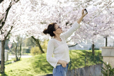 Portrait of mature woman taking photo of tree blossoms with smartphone - FLLF00440