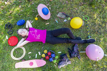 Girl lying on grass, with eyes closed, surrounded by play equipment - SARF04495