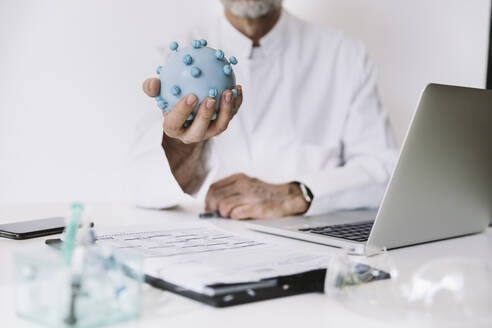 Close-up of scientist holding corona virus model at desk - MFF05205