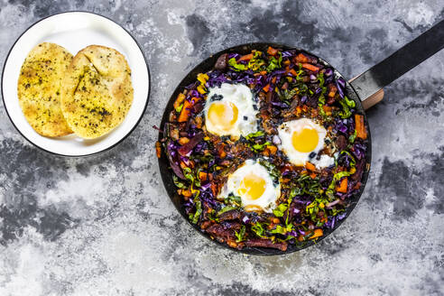 Pan of beetroot shakshouka with chard, carrots, tomatoes, red cabbage and pita bread - SARF04503