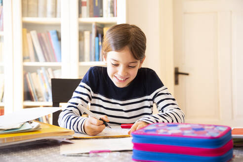 Portrait of smiling girl doing homework - LVF08707